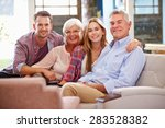 Small photo of Family With Adult Children Relaxing On Sofa At Home Together