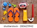 Small photo of high-angle shot of a rustic wooden table full of summer stuff, such as a starfish, a diving mask and a snorkel, a bottle of sunblock, a pair of flip-flops and some beach toys
