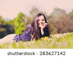 Retro toned portrait of joyful young woman with hand under her chin relaxing on green grass in sunny summer day - stock photo
