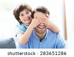 Boy Covering Father's Eyes