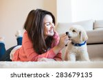 Stock photo woman laying on floor with a puppy 283679135