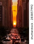 Manhattanhenge in New York City, along the 42nd street. Manhattanhenge is an event during which the setting sun is aligned with the main street grid of Manhattan, New York City - stock photo