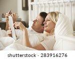 Couple Using Digital Tablet An...