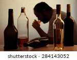 Small photo of silhouette of anonymous alcoholic person drinking behind bottles of alcohol