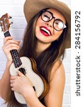 Small photo of Young funny hipster girl having fun and playing on small ukulele guitar, singing and dancing. wearing vintage glasses and straw hat, joy, positive mood. White urban brick wall background.