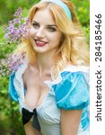 Small photo of Portrait of a beautiful young blonde woman with long hair dressed as Alice in Wonderland. Girl on the nature near the lilac bushes. Soft focus