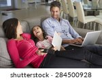 family on sofa with laptop and... | Shutterstock . vector #284500928
