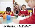 teacher helping female pupil... | Shutterstock . vector #284502005