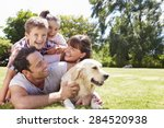 Stock photo family relaxing in garden with pet dog 284520938