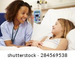 Nurse Sitting By Young Girl's...
