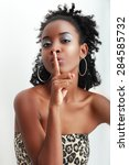 Small photo of Beautiful African American woman with a large afro hairdo making a hushing gesture holding her finger to her lips as she requests silence