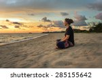 Woman Sitting On Beach Sand An...