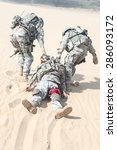 Small photo of United States paratroopers airborne infantrymen in the desert rescuing their brother