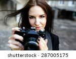 Beautiful female photographer posing with camera - stock photo