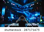 Stock photo dj with headphones at night club party under the blue light and people crowd in background 287171675