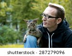 cat sits on the man's lap... | Shutterstock . vector #287279096