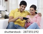Young Man Pointing At Mobile...