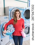 Small photo of looking at camera, young woman holding a laundry basket in launderette