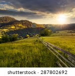 composite rural landscape. fence on the meadow near trees on the hillside. conifer forest on the mountain top in evening light - stock photo