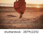 beautiful women in long orange dress is running on the beach at sunset