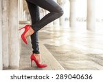Small photo of Woman in black leather pants and red high heel shoes