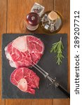 Small photo of Raw fresh cross cut veal shank and seasonings for making Osso Buco on wooden background