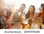 Stock photo group of friends enjoying drink at outdoor rooftop bar 289559648