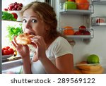 Small photo of woman eats sweets at night to sneak in a refrigerator