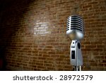 A vintage looking microphone in front of an old brick wall with copy space - stock photo