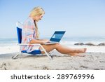 Woman Sitting On Beach Using...