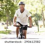 Mature Man Cycling Through Park