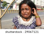 Small photo of A little beggar girl from India standing on the streetside, crying for food.