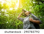 Tourist looking through binoculars considers wild birds in the jungle.Bird watching tours - stock photo