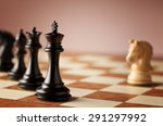 Small photo of Overwhelming advantage - main black chess pieces facing single white knight on a luxurious traditional chessboard in focus