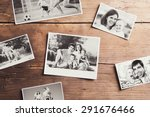 Small photo of Black and white family photos laid on wooden table background.