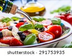 Caprese Italian or Mediterranean salad. Tomato mozzarella basil leaves black olives and olive oil on wooden table.