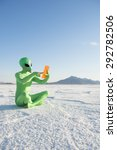 Small photo of Green alien sitting using futuristic tablet computer on dramatic white planet landscape