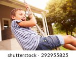 Small photo of Smiling boy swinging on a rope at a playground