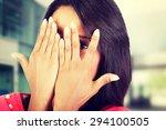 Stock photo shy woman peeking through covered face 294100505