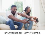Small photo of Happy couple on the couch playing video games at home in the living room