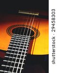 close up of spanish style acoustic guitar in shadows - stock photo
