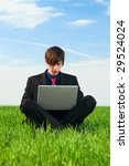 serious man sitting with computer at the green grass - stock photo