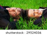 two carefree colleagues resting at the green grass - stock photo