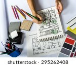 Top view of architects hands drawing of modern house with material sample on creative table top