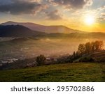 village behind the agricultural meadow with yellow trees on hillside in autumn mountains in sunset light - stock photo