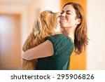 Stock photo dog kissing her owner inside house 295906826