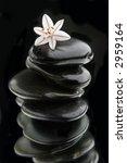 stack of black rocks on mirror - stock photo