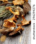 Small photo of Heap of Dried Forest Chanterelles, Porcini and Boletus Mushrooms with Dry Grass and Leafs closeup in Rustic Wooden background
