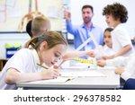 schoolgirl sitting at a desk... | Shutterstock . vector #296378582