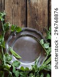 Small photo of Pea and pewter plate on wooden background